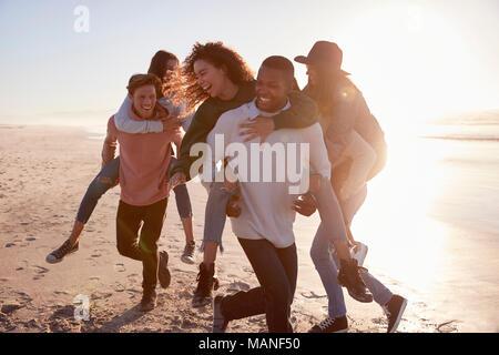 Groupe d'amis ayant la race de ferroutage sur l'ensemble de la plage d'hiver Banque D'Images