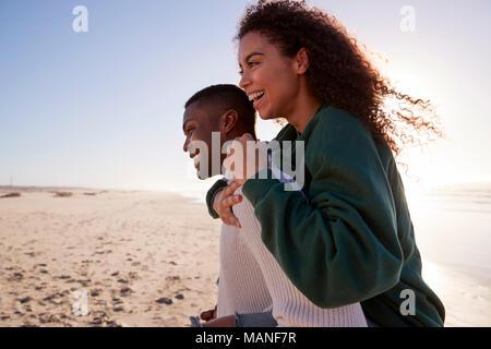 Man Giving Woman Piggyback sur Winter Beach Locations Banque D'Images