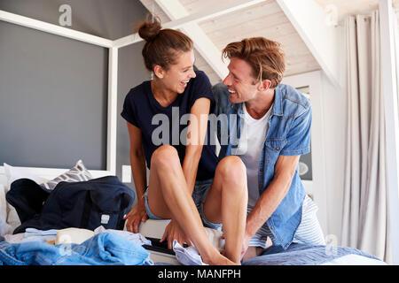 Couple d'essayer de fermer la Maison de valise dans la chambre Banque D'Images