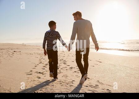 Vue arrière du père et fils marcher sur la plage Main dans la main d'hiver Banque D'Images