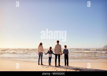 Vue arrière de la famille sur la plage d'hiver se tenant la main à la recherche en mer Banque D'Images
