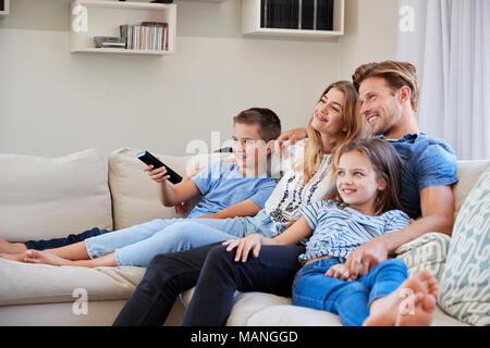 Family Sitting on Sofa à la maison à regarder la télévision ensemble Banque D'Images