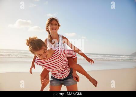 Fille mère portant sur les épaules On Beach Vacation Banque D'Images