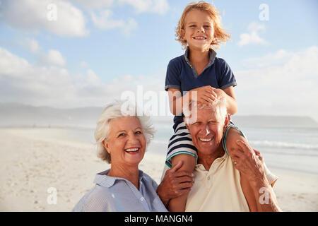 Les grands-parents exerçant son petit-fils sur les épaules sur promenade le long Beach Banque D'Images