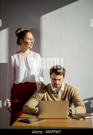 Woman pointing at laptop avec sourire et discuter de quelque chose avec son collègue. Banque D'Images