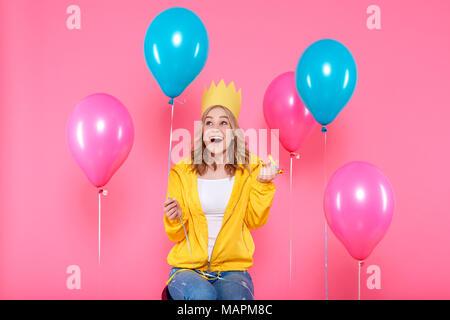 Funny Girl dans anniversaire hat, de ballons et de blowout horn sur fond rose pastel. Adolescent branché attrayants celebrating birthday.