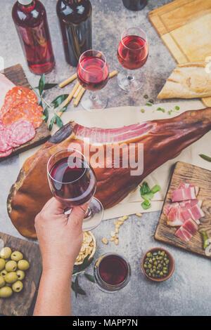 Mans hand holding wine glass frome tableau ci-dessus avec spanit ou hors-d'italien, toute la jambe de jambon serrano et un rouge vin rose. Banque D'Images