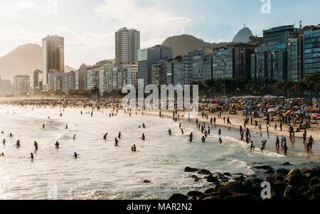 La plage de Copacabana bondée avec vue lointaine du Christ Rédempteur statue d'extrême droite, Rio de Janeiro, Brésil, Amérique du Sud Banque D'Images