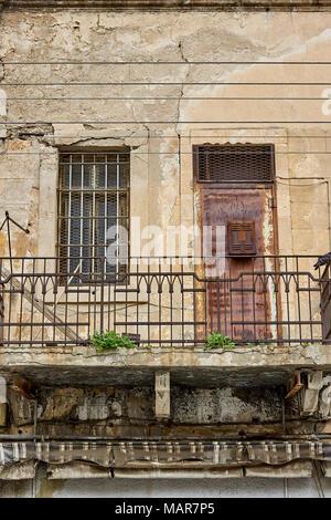 Une porte rouillée et interdit l'ouverture de la fenêtre d'un balcon en ruine Banque D'Images