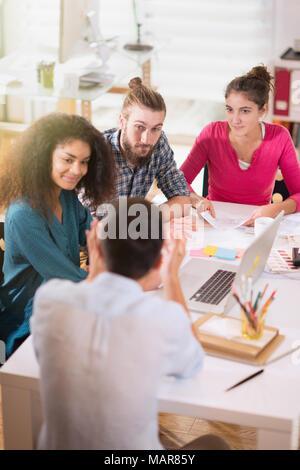 Jeunes collègues de partager des idées en face d'un ordinateur portable.Nouveau projet Banque D'Images