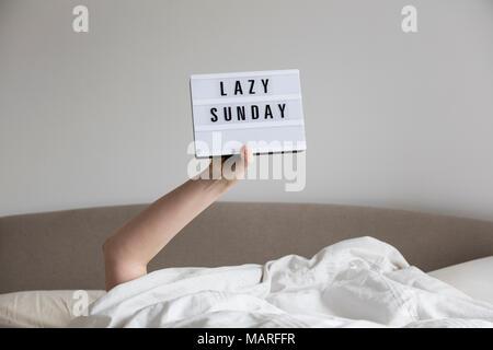 Femme au lit sous les draps holding up a Lazy Sunday sign Banque D'Images