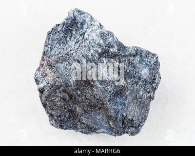 La prise de vue macro des eaux minérales naturelles rock specimen - minerai d'antimoine (Stibnite) pierre sur fond de marbre blanc de l'Ukraine Banque D'Images