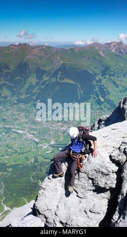 Homme d'alpiniste sur une étroite crête roche exposée sur son chemin jusqu'à la célèbre montagne de l'Eiger dans les Alpes Suisses près de Grindelwald Banque D'Images