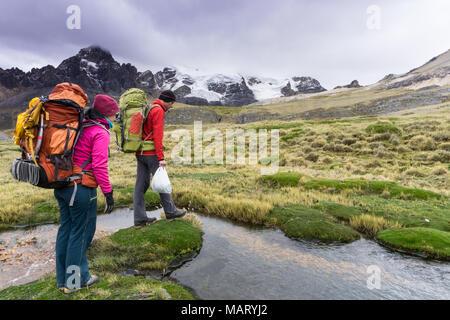Alpiniste mâle et femelle partner préparez-vous à traverser un petit ruisseau dans la Cordillère Blanche au Pérou Banque D'Images
