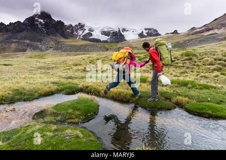 Homme d'alpiniste aide partenaire féminin cross un petit ruisseau dans la Cordillère Blanche au Pérou Banque D'Images