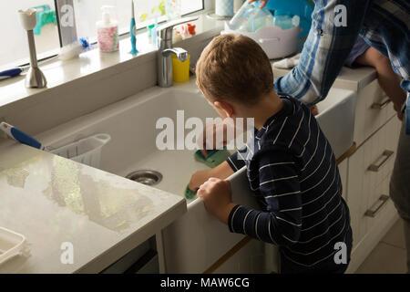 Père et fils dans la cuisine évier de nettoyage Banque D'Images