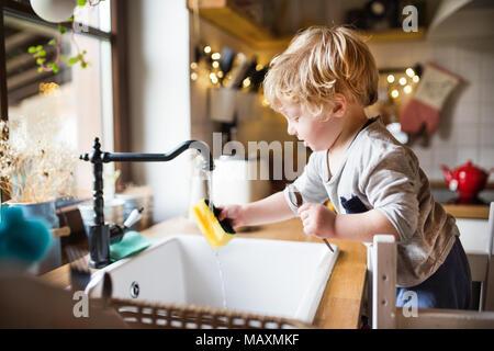 Un bébé garçon lave la vaisselle. Banque D'Images