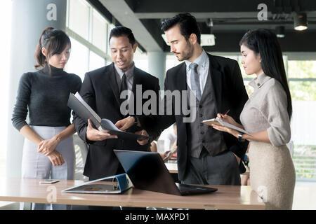 Smart manager expliquant réunion interne à son équipe de projet dans un bureau moderne. Le groupe ethnique de personne d'affaires en litige. Projet et Business c