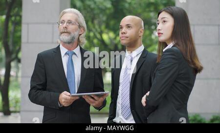 Les cadres d'entreprise multinationale et permanent à la recherche jusqu'à l'immeuble de bureaux modernes. Banque D'Images