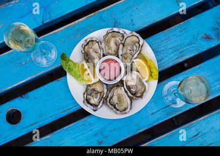 Huîtres et champagne avec citron et mignette vinaigrette en plaque blanche sur bleu distressed vintage table. Banque D'Images