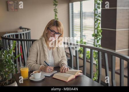Young smiling blonde femme avec des lunettes au restaurant Lire un livre et prendre des notes pendant une pause de travail. Pause café. Moment de détente. Casual woman Banque D'Images