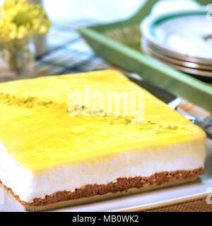 Gâteau au fromage au citron entier non coupé dans un paramètre d'été prêt pour un pique-nique dans un format carré avec copie espace Banque D'Images