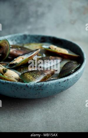 Les moules à Kiwi marinier sauce avec le vin blanc et le persil dans la main, plaque céramique bleu sur fond gris