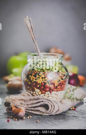 - Légumineuses lentilles pois chiches Haricots Pois verts dans un bocal en verre et des légumes crus. Source de protéines végétaliennes. Des plats végétariens et des aliments sains concept Banque D'Images
