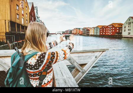 be8d80fcff ... 'Woman taking photo par visite en Norvège smartphone vacances style  scandinave extérieur maisons colorées landmarks '