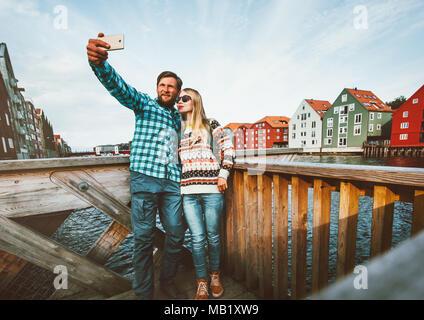 Couple romantique dans l'amour en tenant le smartphone par selfies voyageant ensemble en Norvège vacances week-end en plein air vie maisons scandinaves Trondheim cit Banque D'Images