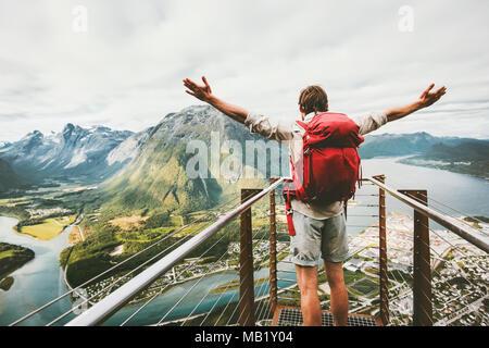 Homme heureux soulevées mains profitant du paysage montagnes aériennes Vie Voyage Vacances aventure émotions succès en Norvège voyageur avec sac à dos stan Banque D'Images