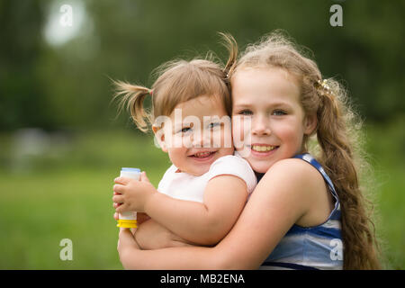 Happy Little Sisters - portrait in park Banque D'Images