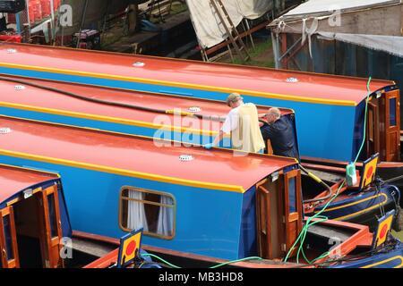 Les hommes qui travaillent sur une péniche / bateau à quai à quai Heyford, Oxfordshire, UK Banque D'Images