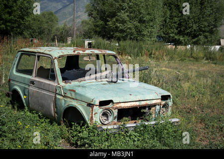 Vieux, abandonnés, ventilées voiture dans un village près de Kolsai Kazakhstan à distance Banque D'Images