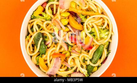 Nouilles aux oeufs sautées avec légumes frais fond rouge Banque D'Images