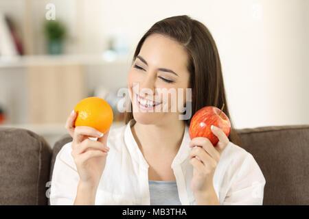 Happy woman décider entre différents fruits assis sur un canapé dans la salle de séjour à la maison Banque D'Images