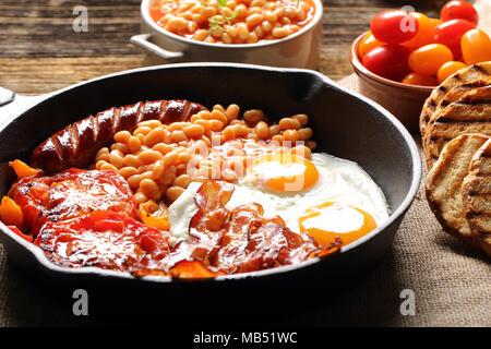 Petit déjeuner anglais avec des saucisses, des tomates grillées, des œufs, du bacon, des haricots et du pain sur la poêle. Banque D'Images