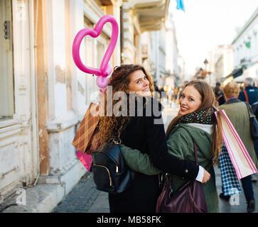 Deux jeunes femmes est satisfait de shopping et marche dans la rue Banque D'Images