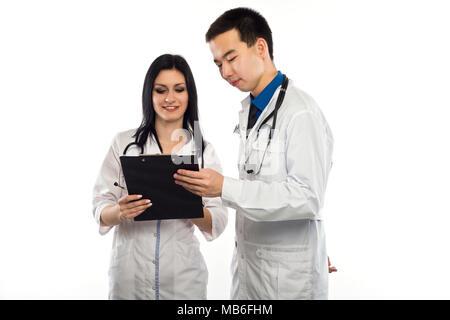 Le personnel médical ayant multiethnique discussion dans un couloir de l'hôpital. Homme et femme nurse wearing blue scrubs travaillant dans une clinique médicale. L'hôpital deux Banque D'Images