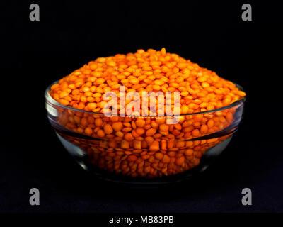 Matières premières lentilles rouges dans un bol en verre. Isolé sur le fond noir Banque D'Images