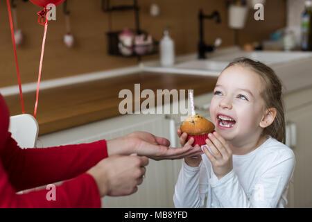 Cute girl bambin célébrer 6e anniversaire. Mother birthday cupcake avec une bougie. Fête d'anniversaire pour enfants concept. Banque D'Images