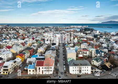 Reykjavik, Islande. La vue au nord-ouest de la tour de l'église Hallgrimskirkja plus vieilles maisons peintes de couleurs vives, regardant vers le bas de la rue Skólavörðustígur Banque D'Images
