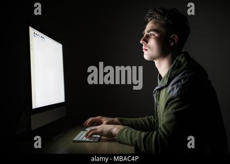 Jeune homme concentré dans les verres à la table et à l'aide d'ordinateur dans une pièce sombre