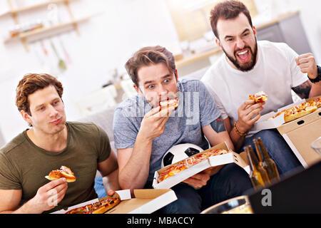 Heureux homme friends eating pizza et regarder la télévision Banque D'Images