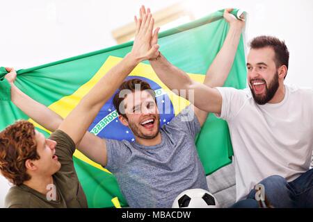 Heureux amis acclamations et regarder du sport à la télévision Banque D'Images