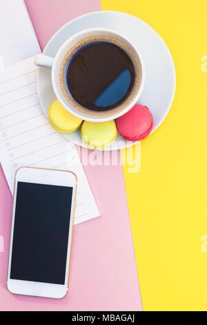 Télévision créative fixer photo de tasse de café avec des macarons et un bloc-notes avec copie espace sur fond jaune et rose style minimal Banque D'Images