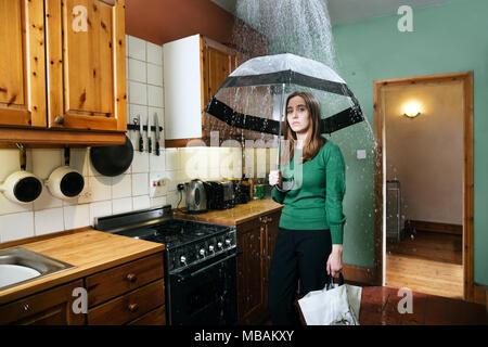 Femme debout dans la cuisine avec un parapluie sous la douche de pluie, à l'intérieur Banque D'Images