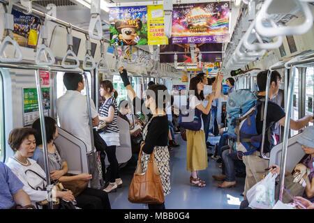 Japon Tokyo Ikebukuro Ikebukuro gare JR Yamanote Line Subway train passagers Asian man woman sitting Banque D'Images