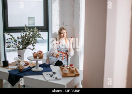 Belle jeune femme manger assis près de cupcake au café de fenêtre Banque D'Images