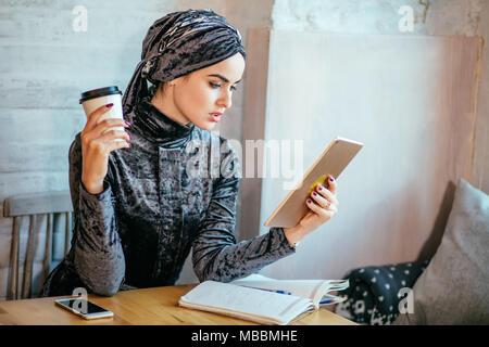 Travailler avec les femmes musulmanes en comprimé et boire un café dans un café Banque D'Images